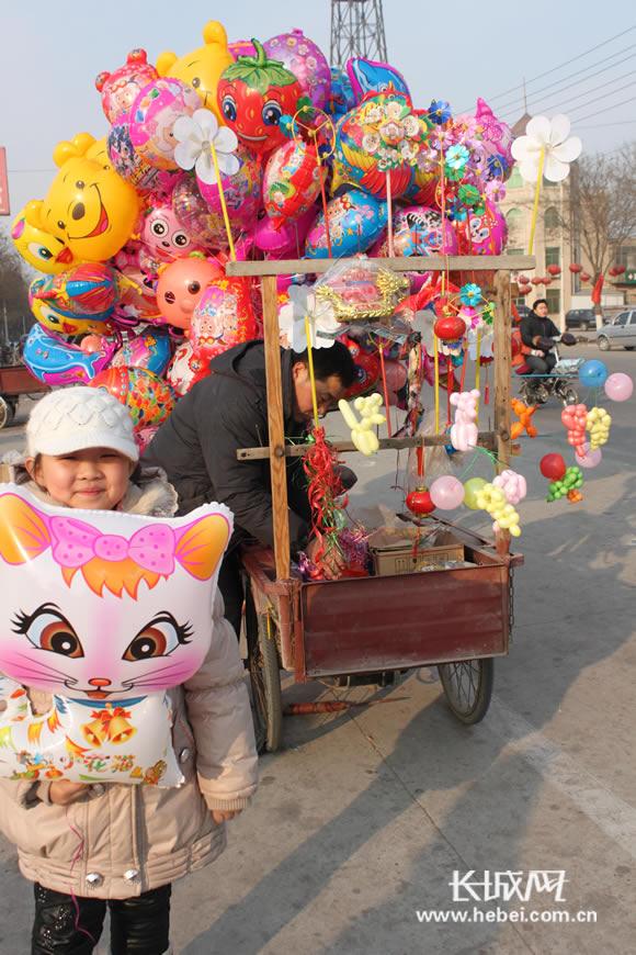 小朋友被街头可爱的氢气球吸引. 长城网 李雪曼 摄