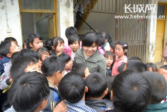 毕节市亮岩镇金华小学的学生们把高岑岑老师团团围住.袁林 提供图片