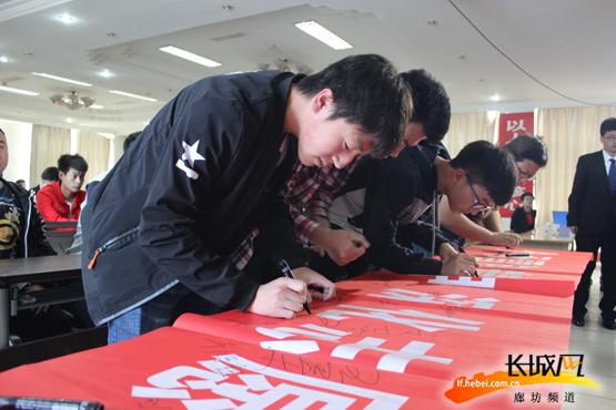 志愿者们在条幅上签字。武香君 摄