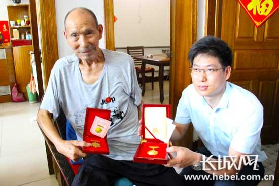 申振新老人向志愿者们展示军功章。