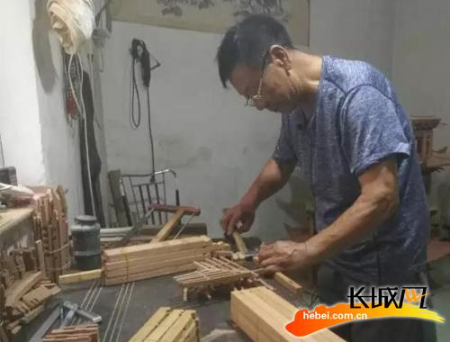 雄安新区工匠邓春江正在制作微缩古建。颖梅 供图