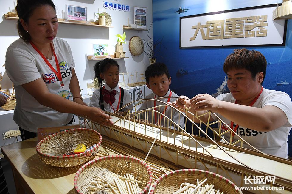 """迁安市大崔庄镇步步川幼儿园的老师和孩子们在制作手工艺品""""两岸同心"""