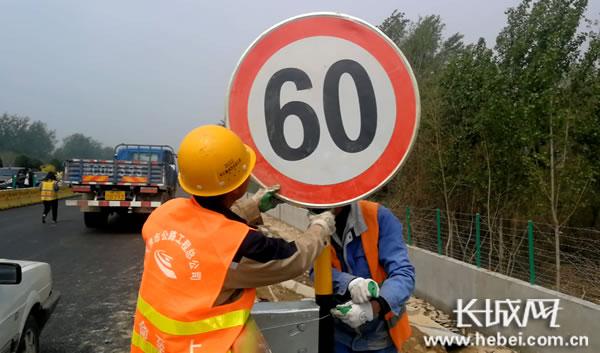 施工工人正在抓紧安装路边标牌。长城网 郭洪杰 摄