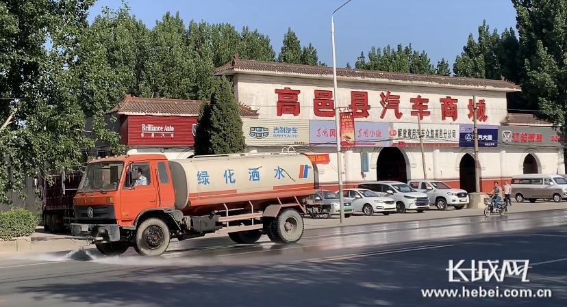 5月20日下午,一辆洒水车在县城西侧的107国道上洒水。本网记者摄