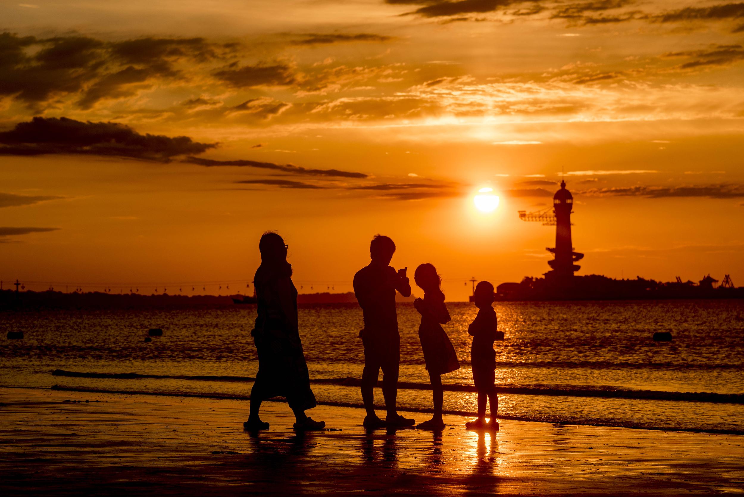 河北秦皇岛:北戴河新区金色阳光映大海 游客海边享受惬意假期