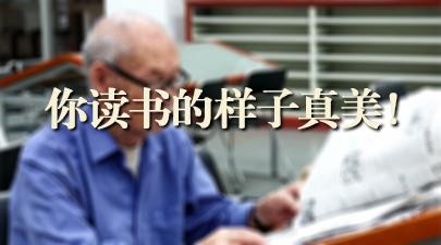 图书馆内,一位头发全白的老人正认真翻阅报纸。