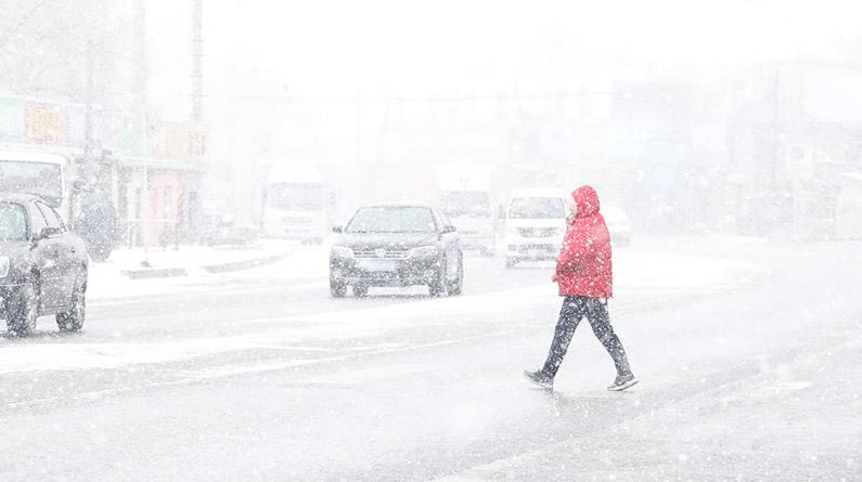 大连迎来降雪天气 市民冒雪出行